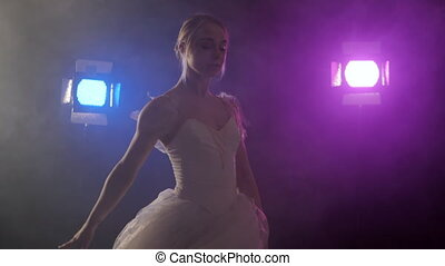 sensual ballerina in white tutu dancing elements of classical or modern ballet, spinning around in the dark with blue and violet light and smoke on floodlights background.