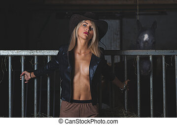 Sensual beautiful blonde woman in the stable with horse