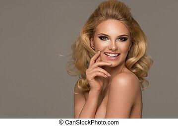 Sensual beautiful blonde woman posing. Girl with long curly hair.