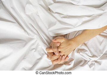 Sensual beautiful young couple is having sex on bed. Female hand pulling white sheets in ecstasy, orgasm. Love concept. Wellness. Couple in love. Orgasm concept