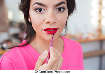 Sensual beautiful young woman applying red lipstick to her lips