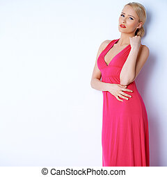 Sensual blond woman posing in pink dress