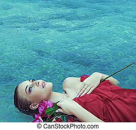 Sensual blonde lying in a clear water