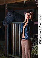 Sensual blonde peasant girl in the stable with horse