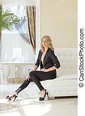 Sensual blonde sitting on white leather couch