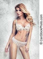Sensual blonde woman in lingerie posing.