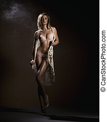 Sensual blonde woman posing in black sensual lingerie with...