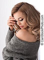 Sensual blonde woman posing in studio, looking at camera