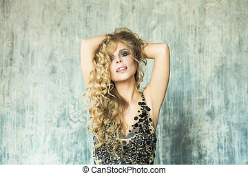 Sensual Blonde Woman with Long Wavy Hair Posing on Bright Background