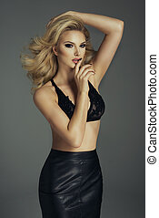 Sensual blonde woman with perfect body posing in studio, looking at camera