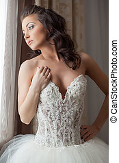 Sensual bride looking dreamily at window