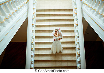 Sensual bride on the stairs in the wedding day