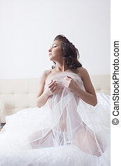 Sensual bride posing topless on bed in hotel room