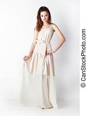 Sensual bright brunette in beige dress