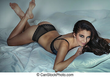 Sensual brunette in lingerie relaxing in bed.