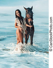 Sensual brunette lady walking with the majestic horse
