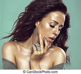 Sensual brunette woman posing in jewelry.