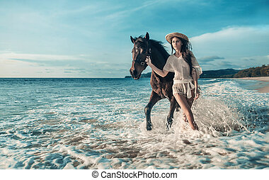 Sensual brunette woman walking with a majestic horse