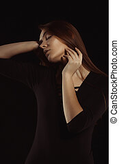 Sensual brunette woman with long hair posing in the shadows at studio