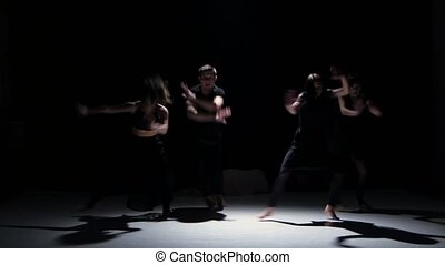 Sensual contemporary dance moves of five dancers on black, shadow