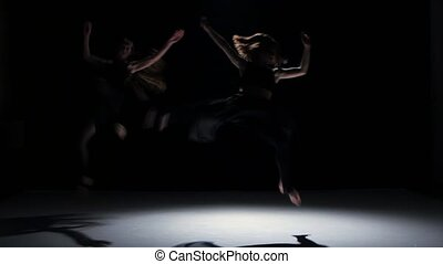Sensual contemporary dance performance of four dancers on black, shadow