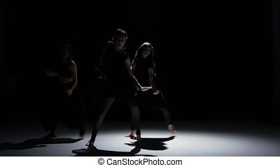 Sensual contemporary dance performance of three dancers on black, shadow