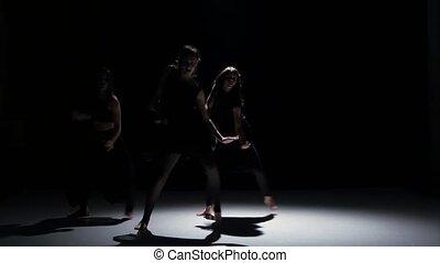 Sensual contemporary dance performance of three dancers on black, shadow