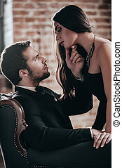 Sensual couple. Beautiful young woman in cocktail dress leaning to her boyfriend sitting in chair and holding his hand on her chin while looking at each other in loft interior