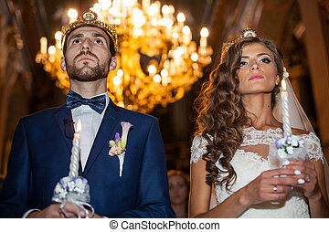 Sensual couple of newlyweds holding candles in church during wedding ceremony