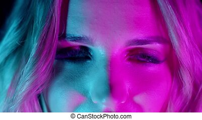 Sensual emotional blonde girl with bright makeup slowly opening eyes in pink green neon lights. Nightlife, nightclub, discotheque concept extreme close-up, 4k footage. Slow motion