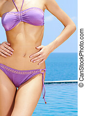 Cropped image of a female hand resting lightly on the curvy buttocks of a woman in a bikini against blue sky.