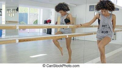 Sensual female practicing her dance moves in studio