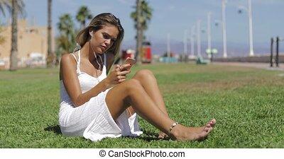 Sensual girl listening ot music on lawn - Young wonderful...