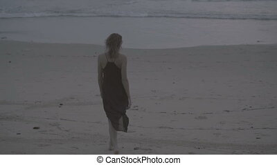 Sensual glamour woman in black dress and wet hair on a beach