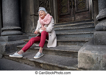 Sensual mature woman relaxing on stairs of historic building