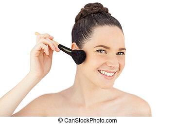 Sensual model using blusher brush while posing on white background