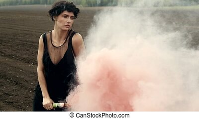 Sensual model with colored smoke on nature