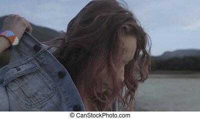Sensual model with pink curly hair in denim jacket posing...