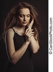 sensual, morena, modelo, em, vestido preto, com, cabelo ondulado, movimento