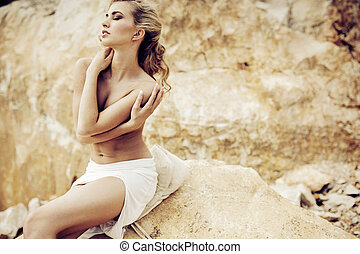 Sensual pale lady posing over the rocks