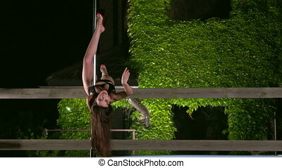 Sensual pole dance performance at night in the summer