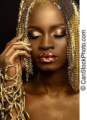 Sensual portrait of sexy african american female model with glossy makeup and golden paillettes wig. Fashion Vogue concept