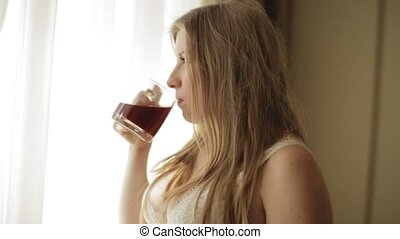 Sensual pregnant woman in underwear drinking tea and thoughtfully staring out window. Slow motion