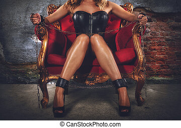 Sensual provocation of a sexy bdsm woman on an armchair -...