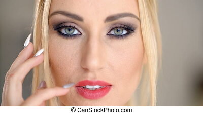 Sensual seductive blond woman with her finger to her parted...
