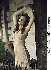 Sensual sexy woman posing next to the wooden house