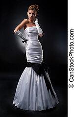 Sensual slender bride in white wedding dress posing in studio