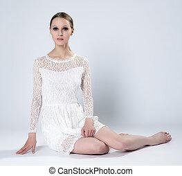 Sensual slim woman posing sitting in studio