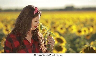Sensual smiling woman posing in sunflower field