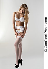 Sensual underwear model straightens stockings - Image of...
